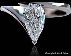 A Single Stone Pear Shaped Diamond Wishbone Cross-over Style Engagement Ring Mounted in Platinum