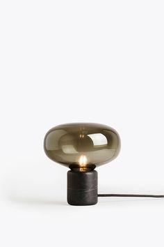 Karl-Johan är en bordslampa med en design inspirerad av svampens organiska form, precis som namnet antyder. Denna härliga lampa är formgiven av Signe Hytte för New Works och finns i två varianter. Välj din Karl-Johan i vitt opalglas med en bas i rökt ek för kontrast eller en vacker kombination av rökigt glas med en bas i marquinamarmor.