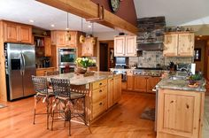 Kitchen with new cabinets, new stainless steel appliances, a travertine tile backsplash and granite counters. There's an island with storage and seating, double in wall-ovens, a built-in microwave and a six-burner gas range.