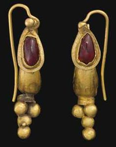 A PAIR OF ROMAN GOLD AND GARNET EARRINGS CIRCA 2ND CENTURY A.D. Each boat-shaped, tapering at the ends to wires that form the closure, fronted by a drop-shaped box set with a garnet, a single granule above with a small loop at the back, a rigid pendant below composed of a cylindrical ribbed collar supporting a cluster of five hollow spheres; joined to a modern earwire