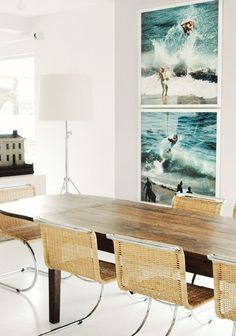 Woven chairs at a wood table with surf and ocean art prints.