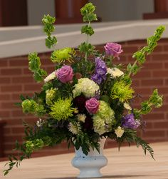 Church flowers: bells of Ireland, cool water lavender roses, green hydrangea, black baccara roses, lavender stock