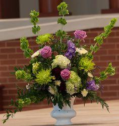 Church flowers: bells of Ireland, cool water lavender roses, green hydrangea, black baccara roses, lavender stock