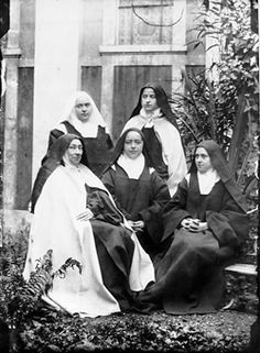 Standing are Therese' sisters Celine and Pauline; seated are Mother Marie de Gonzague, Marie, and Therese. Photograph taken in the Courtyard at Carmel Lisieux, early 1895.