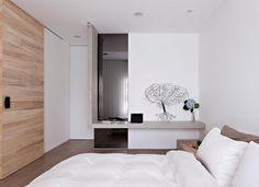chambre adulte avec un grand lit et coussins et déco murale arbre