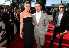 His girl pulled it off: Nick Jonas wore a plaid suit in grey and yellow with blue but his ...
