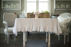 A White Linen Tablecloth Measuring X With A 6 Inch Ruffle Included In The  Size.