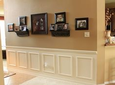 Great way for a hallway, love the how the pictures hang on the wall and the paneling to break it up