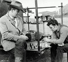 "John Wayne and son Patrick during a break on the set of ""Mcklintock""."