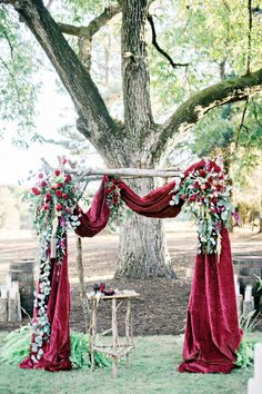 Wedding ceremony backdrop with red roses, greenery and apples