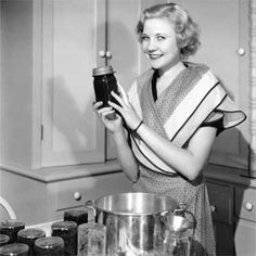 1940s: Preserving for the Future | The American Kitchen Through the Ages | This Old House.  old photo of a woman holding up a filled canning jar