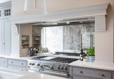 10 Elegant Tile Backsplash Behind The Stove Ideas backsplash behind the stove, kitchen design, mirror backsplash, white cabinets Antique Mirror Splashback, Mirror Backsplash Kitchen, Stove Backsplash, Antiqued Mirror, Kitchen Soffit, Mirror Mirror, Countertop, Kitchen Cabinets, Luxury Kitchens
