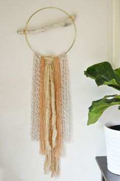 "Cotton and wool in gorgeous blush tones hang on a golden hoop with driftwood from the Washington coast.One of a kind, and created with 100% USA sourced materials.Measures 42"" long and 15"" wide at driftwood.Ships priority with tracking within 2 days. Upon arrival, the hanging may need some fluffing and straightening from travel. To hang simply use a small nail, or a hook hanging from the ceiling."