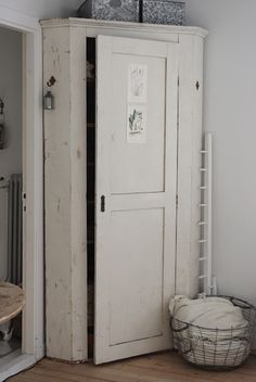 A TALL CORNER CUPBOARD.KNOCK OUT THE BOTTOM FOR TREADMILL STORAGE?