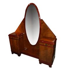 French Art Deco Dressing Table in exotic walnut and cherry wood with an oval center mirror with and a small drawer above a cabinet door on both sides of mirror. Stamped Majorelle Nancy; France, c. 1930
