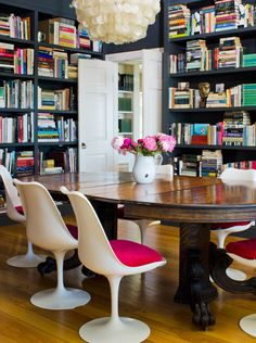 Tulip chairs in the dining room, with bookshelves surrounding from floor to ceiling.