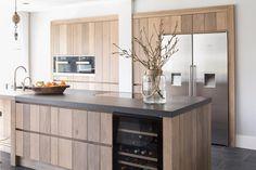 Een houten keuken met openslaande deuren naar de tuin en een ruim kookeiland met…
