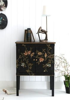 A small black foyer console table/chest that has birds and flowers painted on it with an antique lamp and books on it. Great contrast against white walls.