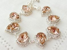 Blush Pink crystal teardrop earrings, Drop earring, Swarovski Rhinestone Halo Earrings, Bridal earring, Bridesmaids gift, Dangle, Silver or gold  Elegant and refined.  These earrings have a wonderful soft vintage pink center stone surrounded by clear crystal stones - so much sparkle. They would be great as bridal earrings or for any other day. Perfect gift for bridesmaids or other occasions.  They are made of silver plated plated brass posts and Swarovski crystals, all set in prong setting…