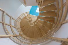 Para criar a circulação vertical, o projeto da casa Mosha em Teerã, Irã, recorreu a um recorte circular a fim de acomodar a escada helicoidal (caracol) em madeira clara. A casa tem a assinatura do escritório New Wave.  Fotografia:  Architecture. Parham Taghioff /  Divulgação.  http://estilo.uol.com.br/casa-e-decoracao/album/2016/09/09/vista-espetacular-e-terreno-em-declive-determinam-projeto-de-casa-escultura.htm?foto=13