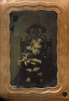 post mortem image of a deceased child~the childs blank stare to the side, paired with his being tied to the chair, his mothers hands can be seen behind the chair trying to hold his head upright. The Baby's mother or the Photographers assistant (and the Photographers belt) is holding the very much alive baby still for the long exposure.