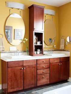 Above-the-Counter Storage:  For an easy and inexpensive solution, consider retrofitting an existing vanity with a storage unit placed on the countertop. Here, a slender but versatile piece of cabinetry sits between the vanity's two sinks, providing open and closed storage at arm's length.