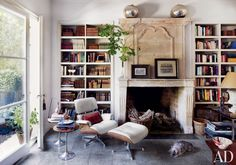 In the library of a Madrid home, an Eames lounge chair and ottoman sit next to a 17th-century French chimneypiece.