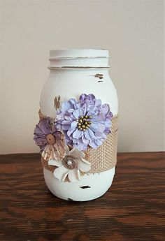 This gorgeous mason jar would be a lovely addition to your home. Use it alone as a cute home accent, or utilize it as a stylish container! This jar is painted in vintage white and is embellished with burlap ribbon and paper flowers. Each jar is painted with three coats of acrylic paint and then distressed to look aged. It is then sprayed with a sealant. The inside of this jar is safe for use of water, but getting the outside of this jar wet may cause damage to the paint and/or embellis...