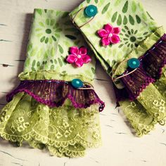 Bright fun colors of layered French lace and hand stitched accented by hot pink rosettes and funky buttons.