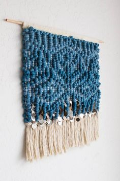 This tapestry is made with a gorgeous indigo corespun yarn. The yarn is a blend of merino and recycled water bottles! Over 200 pewter and bronze sequins in all sizes border the bottom above a bottom row of 100% thick cotton fringe. My favorite thing about this piece is that the effect