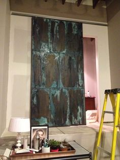 DIY Faux Aged Metal Door (made out of foam insulation boards) - Full Tutorial includes how to construct the door and products and steps used to achieve the faux metallic finish.