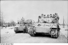 Tiger receiving supplies from a turretless ammunition carrier (Panzer III chassis?). Winter 1944.