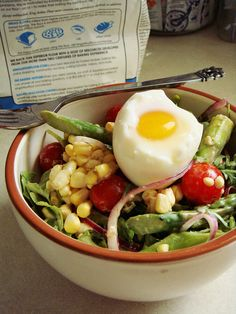 Light lunch salad of asparagus, arugula, fresh corn, cherry tomato, red onion, and soft-boiled egg in a red wine vinegar sour cream dressing.