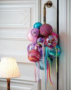 Uma opção à tradicional guirlanda é preparar um arranjo para pendurar na maçaneta da porta principal. Este modelo tem bolas de Natal e fitas