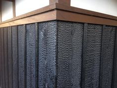 Traditionally, trim is often a slightly different color than the yakisugi (shou sugi ban) field. In this case it is intermediate between the jet black Suyaki and natural plaster upper wall.