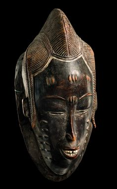 """Africa   Anthropomorphic face mask """"gu"""" from the Guro people of Ivory Coast   Wood; dark brown patina, whitened teeth and remains of red paint on the lips   ca. 1970s    """"gu"""" is always presented as a young woman, who is considered to be zamble's wife. During the masquerade she appears after the two zoomorphic masks """"zaule"""" and """"zamble"""", accompanied by flutes, moving slowly and charming, singing in honour of """"zamble""""."""