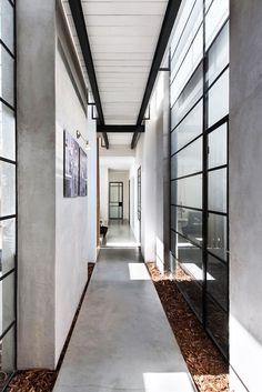 """This beautiful industrial chic home in Tel Aviv, Israel, was planned for a family of four. Architect studio NeumanHayner designed two cubes separated by a passage, creating an """"L"""" shaped house. The fr"""