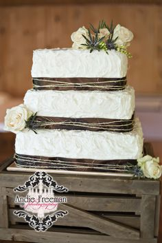 Country wedding cake with pale pink roses and burlap twine on vintage crate.
