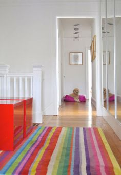 White walls, red furniture, bright striped rug...love the style!