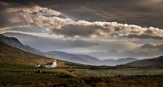 Small church in the Icelandic countryside, taken from the middle of a cow paddock