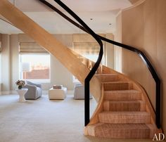 The curving staircase, which has balustrades of glass and English sycamore, at Steve Wynn's Manhattan duplex.