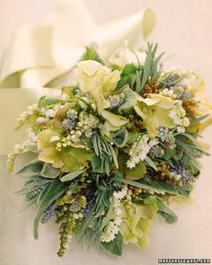 This bouquet has a variety of textures and colors, thanks to the mix of muscari (grape hyacinth), lamb's ear, lily-of-the-valley, andromeda, helleborus, thyme, rosemary, sage, and scented-geranium foliage.