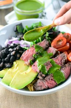Chimichurri Steak Bowl loaded with sliced ribeye, avocado, tomatoes, red onion, black beans, spanish rice and lettuce then drizzled with chimichurri.