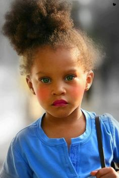 This afro turned into a beautiful spunky bun is absolutely adorable on this gorgeous mixed kid with green eyes.