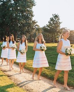 Bridesmaids walk the aisle wearing crisp white dresses accented with pink stripes.