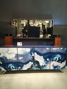 This credenza features a blue top and frame, but the star detail is the wallpaper that wraps the cabinet doors of this John Strauss piece.
