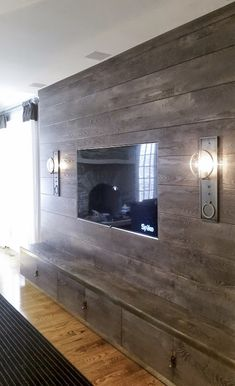 Custom wall built-in for a client of Michele Plachter Design of Philadelphia. Gray stained textured solid Ash horizontally planked TV wall with inset doors and brass details.
