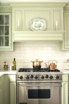 Mantel-Style Range Hood: The vintage-style vent hood meshes perfectly with the cabinetry, bringing the kitchen together. The stainless-steel range adds a contemporary twist while retaining the kitchen's elegant style. Green Kitchen, Kitchen Redo, Home Decor Kitchen, New Kitchen, Home Kitchens, Kitchen Remodel, Kitchen Cabinets, Kitchen Appliances, Kitchen Ideas