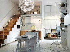 aménagement sous escalier avec rangements cachés, cuisine en bois et blanc et sol en parquet blanchi