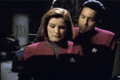Janeway and Chakotay - he just told her that she fiddles with her comm badge when she's nervous, so she's making fun of it!